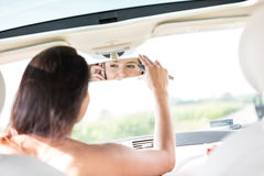 Woman adjusting rearview mirror while using mobile phone in car Stock Photography