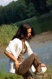 Woman adjusting shoe by lake Stock Photo
