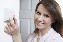 Woman Adjusting Thermostat On Central Heating Control. Smiling Woman Adjusting Thermostat On Central Heating Control Royalty Free Stock Photography