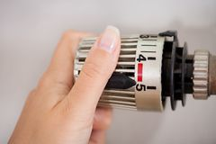 Woman Adjusting The Thermostat Stock Images