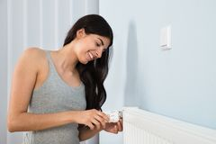 Woman adjusting thermostat on radiator Royalty Free Stock Images