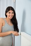 Woman adjusting thermostat on radiator Stock Photography
