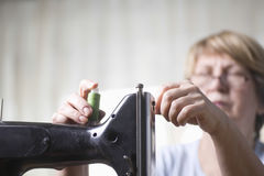 Woman Adjusting Thread On Sewing Machine Royalty Free Stock Photo