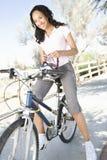 Woman Adjusts Cycling Helmet On Mountain Bike Stock Photo