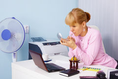 Woman adjusts makeup in office Stock Images