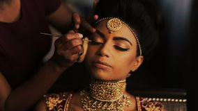 Woman adjusts makeup on stunning face of Indian bride while she sits calm on the chair