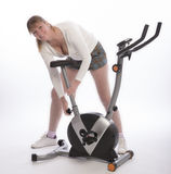 Woman adjusts saddle on exercise bike Stock Photo