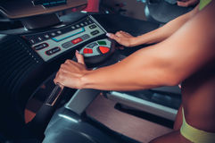 Woman adjusts the treadmill at the beginning of training Stock Photo