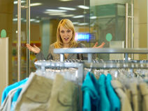 Woman is admired by clothes. The young beautiful woman has come to a lady's wear shop and is surprised  fine choice Stock Images