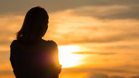 A woman admires a beautiful sunset, the view from behind