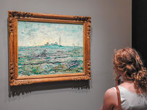 A woman admires a painting by Van Gogh Stock Photo