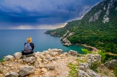 Woman admiring the beauty of the Olympos beach. Female trekker resting on a rocky outcrop above the beautiful Olympos beach and bay in Turkey Royalty Free Stock Photography