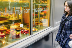 Woman admiring French sweet pastry food. STRASBOURG, FRANCE - MARCH 21, 2015: Woman admiring French sweet pastry food in typical French boulangerie saloon Stock Photos