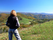 Woman admiring a mountain land. Woman on a mountain looking over a mountain landscape with fall foilage on trees Stock Images