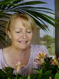 Woman Admiring New Blooms. A middle-aged smiles as she admires the new blooms on the plants in her fernery Stock Photo