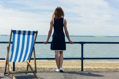 Woman admiring the sea from promenade with a deck chair Royalty Free Stock Image