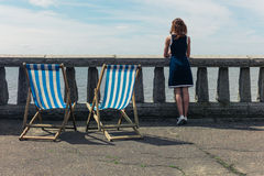 Woman admiring the sea from promenade with deck chairs. A young woman is standing by a wall with concrete balustrades on a promenade and is admiring the sea Royalty Free Stock Photography