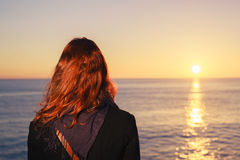 Woman admiring the sea at sunset Stock Photo