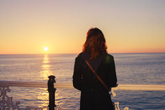 Woman admiring the sea at sunset Stock Image