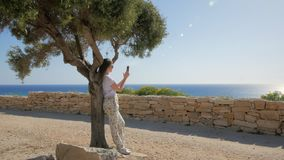 Woman is admiring sea views and photographing by mobile phone, leaning on trunk of tree