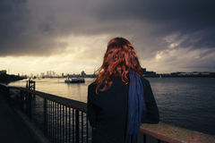 Woman admiring sunet over river in city Stock Image