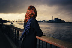 Woman admiring sunet over river in city Stock Images