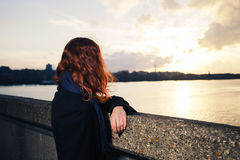 Woman admiring sunet over river in city Royalty Free Stock Photography