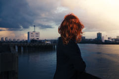 Woman admiring sunet over river in city Royalty Free Stock Images
