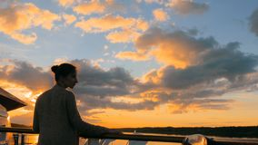 Woman admiring sunset from deck of cruise ship. Woman standing on deck of cruise ship and looking at landscape. Sunset light, golden hour. Nature and journey royalty free stock photo
