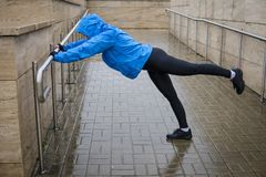 Woman adult doing bodyweight glute and leg exercises on outdoor. In the rain. Fitness woman doing donkey kick exercise for glutes strength training Stock Photos