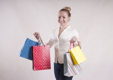 Woman adult   smile shocked  fashionable  a jacket in   housewife packages for purchases studio. Woman elegant   a jacket in    packages for purchases studio Royalty Free Stock Images