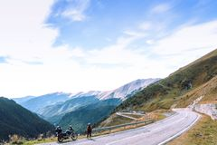 Woman with adventure motorcycle. Motorbike rider. Top of mountain road. Motorcyclists vacation. Travel and active lifestyle. Transfagarasan Romaia, copy space royalty free stock photos