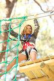 Woman in adventure park. Young beautiful blonde woman climbing roped up in adventure park Stock Image