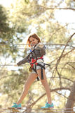 Woman in adventure park. Happy young beautiful blonde woman climbing roped up in adventure park, smiling to the camera Royalty Free Stock Photo