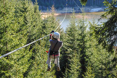 Woman in adventure park. Woman sliding on a zip line above the trees in an adventure park Royalty Free Stock Photography