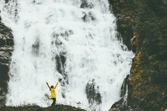 Woman adventurer happy raised hands enjoying big waterfall royalty free stock photo