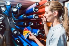 Woman in advertising material production looking for the right film color. Checking it with fan stock image