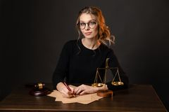 Woman advocate sign judicial documents, State of Justies is on the table in front of nice woman advocate, advocate. Concept, black dressed young woman advocate stock image