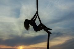 Woman climbs up the rope. Woman aerial acrobat climbs up the rope Stock Photo
