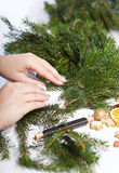 Woman affixing branches on Christmas wreath Stock Image