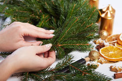 Woman affixing branches on Christmas wreath Royalty Free Stock Photo
