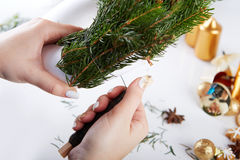 Woman affixing branches on Christmas wreath Stock Photos