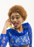 Woman with african appearance in blue dress speak on banana as phone, white background. Mobile connection concept. Lady. With banana near ear. Lady on surprised royalty free stock image