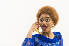 Woman with african appearance in blue dress speak on banana as phone, white background. Mobile connection concept. Lady. On surprised face and afro hairstyle stock photo