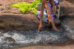 Woman in African outfit on the verge of fluent river. Interactin. G with water. Angola Stock Photo