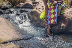 Woman in African outfit on the verge of fluent river. Interactin. G with water. Angola Royalty Free Stock Images