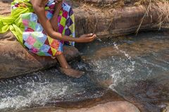 Woman in African outfit on the verge of fluent river. Interactin. G with water. Angola Royalty Free Stock Image