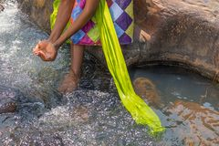 Woman in African outfit on the verge of fluent river. Interactin. G with water. Angola Stock Photos