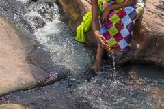 Woman in African outfit on the verge of fluent river. Interactin. G with water. Angola Royalty Free Stock Photos