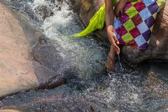 Woman in African outfit on the verge of fluent river. Interactin. G with water. Angola Stock Images